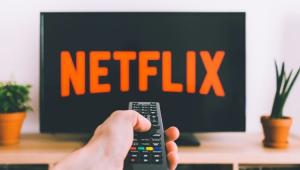 Televisão cMão de uma pessoa usando um controle remoto em frente a uma TV da Netflix
