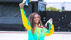 Rayssa Leal levantando um buquê de flores e com a medalha de prata na outra mão