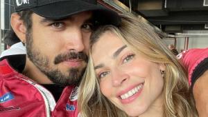 Caio Castro com roupa de piloto abraçado com Grazi Massafera