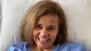 Claudia Rodrigues sorrindo deitada em uma cama de hospital