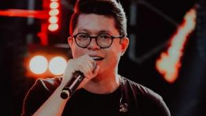 DJ ivis, homem branco com óculos redondo preto e cabelo castanho de topete, cantando com microfone