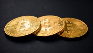 Três moedas de bitcoin são sobrepostas em uma superfície cor de chumbo