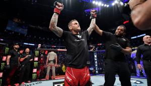Homem segura a mão de lutador de UFC que ganhou a partida e está no octágono