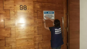 Fiscal da Vigilância Sanitária fixa placa de interditado em porta marrom