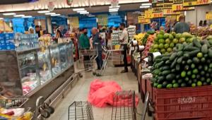 Corpo de uma mulher coberto por plástico rosa no meio do corredor do supermercado Supermarket em São Conrado, no Rio de Janeiro