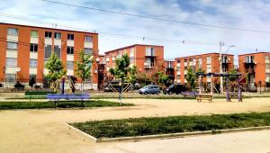 Três edifícios de três andares quadrados de cor laranja, um ao lado do outro. Na frente, palmeiras e alguns carros. Uma praça com árvores, canteiros e areia