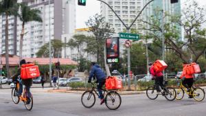 Quatro entregadores em cima de bicicletas em uma rua com bags da Rappi