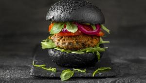 Imagem de frente de um sanduíche de hambúrguer vegetariano com pão preto colocado uma mesa cor de chumbo