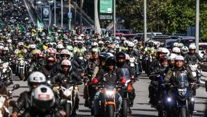Várias pessoas de moto, incluindo o presidente Jair Bolsonaro, andando em rua de São Paulo