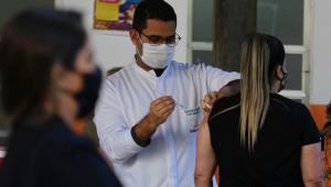 De jaleco, profissional de saúde aplica vacina em uma mulher