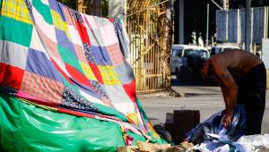 Homem em situação de rua se agacha e remexe o lixo ao lado de uma barraca formada por cobertores