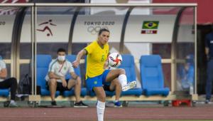 De camisa amarela, calção azul e meião branco, a jogadora Tamires, da seleção brasileira, se prepara para dominar a bola com a perna esquerda