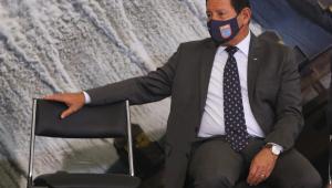 Usando termo cinza, camisa branca e máscara de proteção, Hamilton Mourão aparece sentado ao lado de uma cadeira vazia