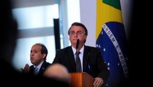 De traje social, o presidente Jair Bolsonaro discursa com a bandeira do Brasil atrás e seu intérprete de sinais do lado