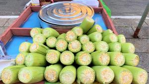 Carrinho com várias espigas de milho verde e uma panela de pressão