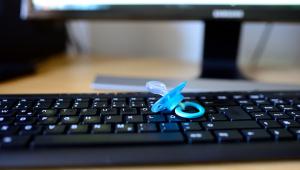 chupeta em cima de um teclado de computador