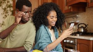 Jovem casal negro lado a lado na cozinha; o homem segura os óculos e tenta ver o que a mulher olha sorridentemente para o celular