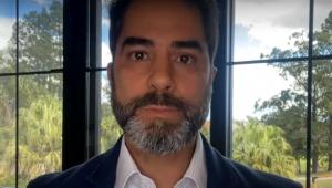 Victor Sorrentino usa terno, camisa social branca, com barba grisalha e paisagem verde ao fundo