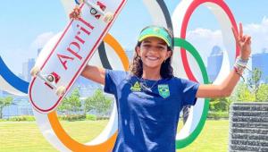 Rayssa Leal está de camisa azul e boné verde, erguendo um skate com o braço com o símbolo olímpico ao fundo