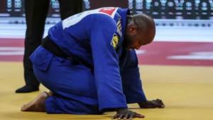Jorge Fonseca se debruça no tatame com um kimono azul escuro