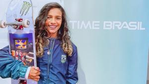 Rayssa Leal tem cabelos castanhos longos e segura um skate colorido e sorri ao fundo de uma parede com os escritos 'Time Brasil'