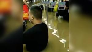 Pessoas com água na cintura dentro de metrô na China
