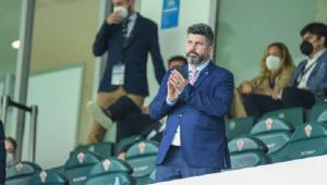 Homem de terno azul em pé em um estádio de futebol com cadeiras. Tem as mãos juntas e olha para o horizonte. Algumas pessoas estão atrás sentadas e em pé