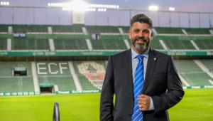Homem posando para a foto sorrindo com uma mão no terno preto. Usa gravata listrada azul e branca e tem barba e cabelos grisalhos