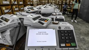 Sala com mesa cheia de urnas eletrônicas que seriam usadas nas eleições
