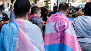 Duas pessoas cobertas por Bandeira do Orgulho Transgênero em uma manifestação na Espanha