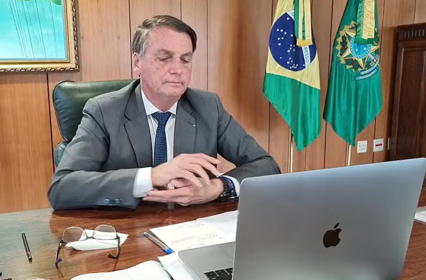 jair bolsonaro sentado em cadeira e olhando para computador