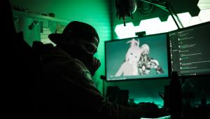 Homem jogando um jogo. Não dá para distinguir o rosto dele porque as luzes são escuras e verdes. No computador, duas telas, uma com conversas e otura com personagens de anime