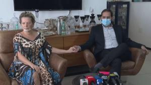 Sentados no sofá, Joice Hasselmann, de vestido florido e a cara com alguns hematomas, dá a mão para o marido Daniel França, vestido em trajes sociais