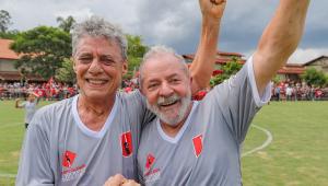 Dois homens com camisetas cinzas de futebol abraçados com as mãos para cima com um campo de futebol atrás