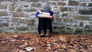 Pessoa sentada em frente a uma parede de touca com a cabeça entre as mãos. Não dá para ver o rosto. Está sentada em folhas secas marrons