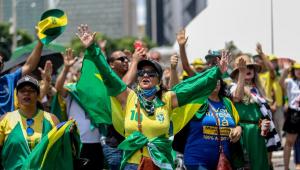 Grupo de manifestantes com camisetas e bandeiras do Brasil