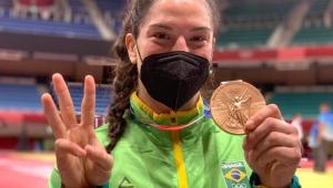 Com o uniforme do Brasil, o cabelo preso com rabo de cavalo, Mayra Aguiar segura a medalha de bronze com a mão esquerda e faz sinal de três com a mão direita
