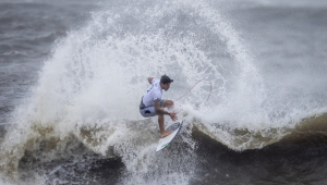 Gabriel Medina, de camiseta branca, completa manobra no mar