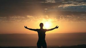 Silhueta de uma mulger na praia, com os braços abertos, em frente ao por do sol