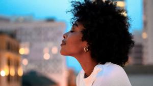 Mulher com rosto pacífico apoiada em janela com os olhos fechados. Ela é negra, tem cabelos crespos e está de perfil
