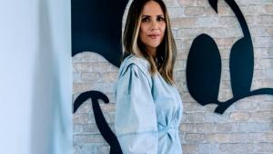 Mulher de cabelos compridos de lado posando para a foto com um vestido azul. Atrás, o desenho de um Mickey na parede