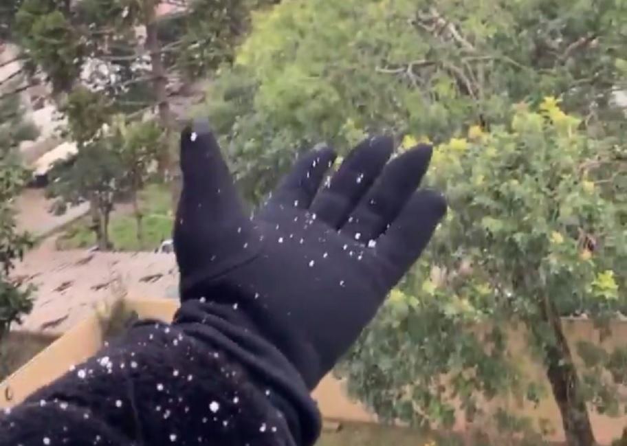 mão com luva segurando neve em gramado