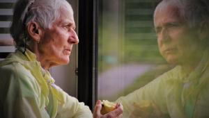 idosa de perfil olhando para fora da janela com olhar pensativo