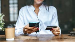 Sentada em frente a um balcão, mulher (que só aparece do nariz para baixo) mexe no celular com a mão direita e segura cartão de banco com a direita