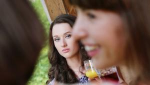 Mulher com cara de poucos amigos olha para uma outra, que está sorridente