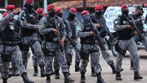 De roupa camuflada, boina vermelha, máscara e fuzil na não, militares da Força de Segurança Nacional caminham por uma rua de Manaus, um perto do outro