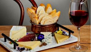 Tábua branca com queijos cortados e pães dentro de uma cestinha. Taça de vinho tinto