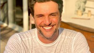 Ator Rodrigo Lombardi, homem branco, de barba curta grisalha e cabelos curtos castanhos, olhando para a câmera e sorrindo. Usa camiseta branca