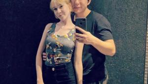Sammy e Pyong Lee abraçados tirando uma foto com o celular. Ela usa uma regata estampada com o Mickey e um shorts preto e ele camiseta cinza e shorts cinza