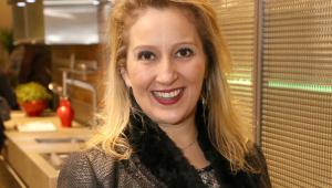 Mulher de cabelos compridos loiros sorrindo e olhando para a câmera. Usa um casaco preto e uma manta preta e está de batom avermelhado. Foto tirada do peito para cima